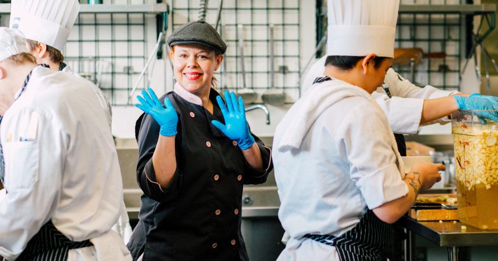 woman chef waving at camera