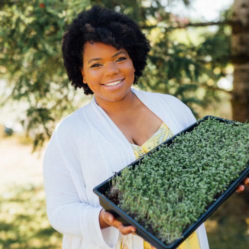 Farmer holding microgreens, smiling